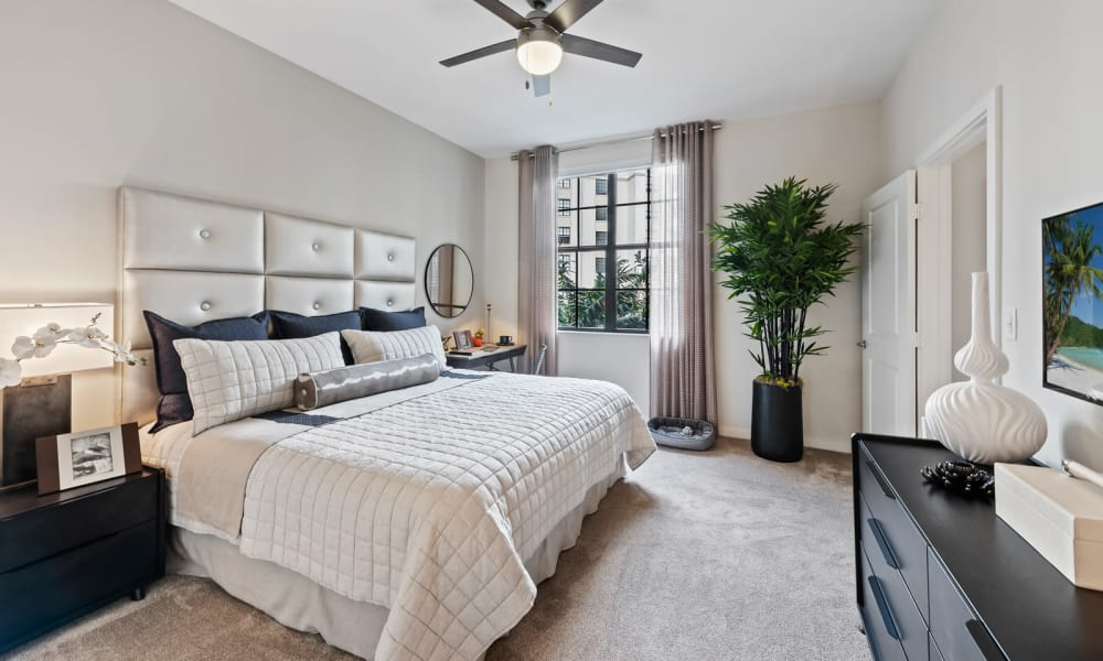 Bedroom with carpet and dark ceiling fan in model home at 6600 Main in Miami Lakes, Florida