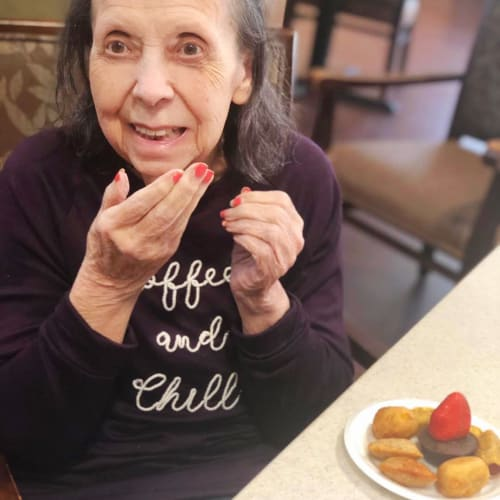 Resident with a plate of desert at Oxford Glen Memory Care at Sachse in Sachse, Texas