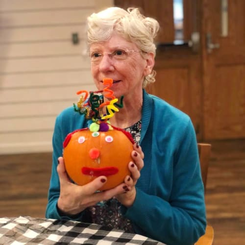 Resident showing off a decorated pumpkin at Oxford Glen Memory Care at Sachse in Sachse, Texas