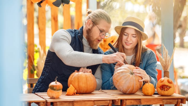 A man and a woman intently carving pumpkins near The Ranch at Shadow Lake