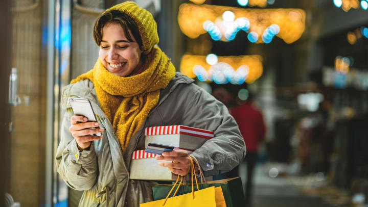 Woman checking smartphone while carrying shopping bags and boxes