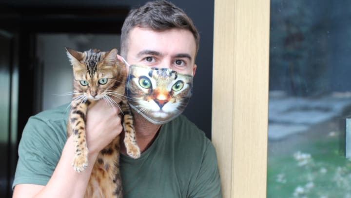 Man holding cat, wearing mask with the cat's face on it.