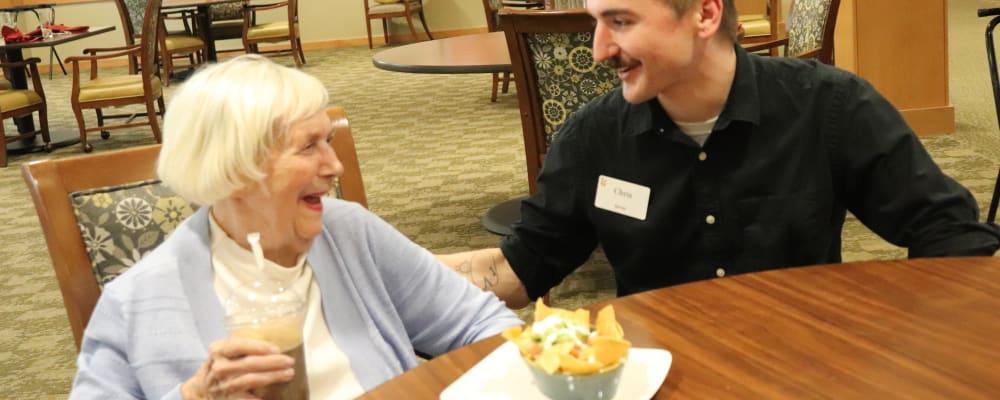 Resident enjoying her meal talking with server at The Springs at Greer Gardens in Eugene, Oregon
