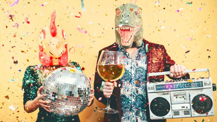 A man and woman wearing animal masks over their heads, stand in a shower of confetti holding a mirror ball, an oversize glass of wine, and a boom box.