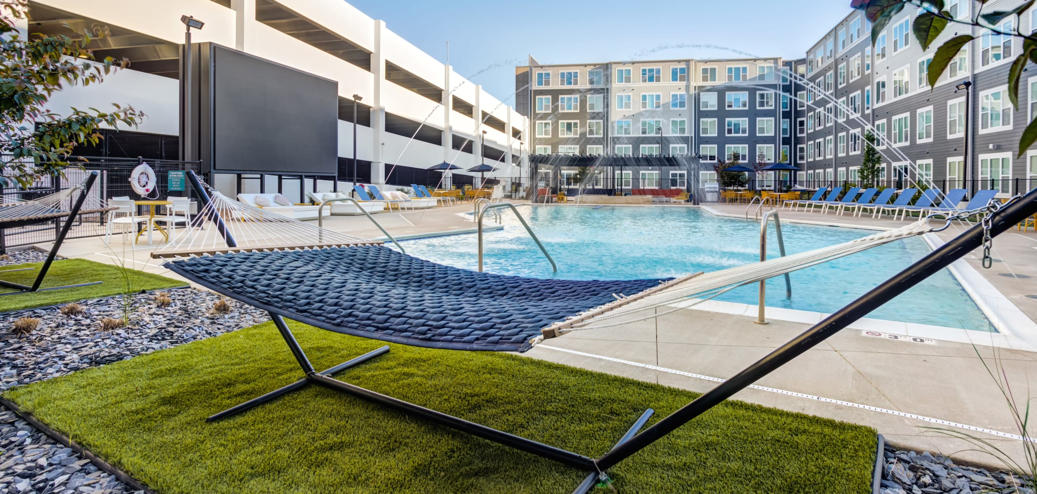 Enjoy Apartments with a Swimming Pool & Poolside Hammocks at LATITUDE at River Landing in Coralville, Iowa