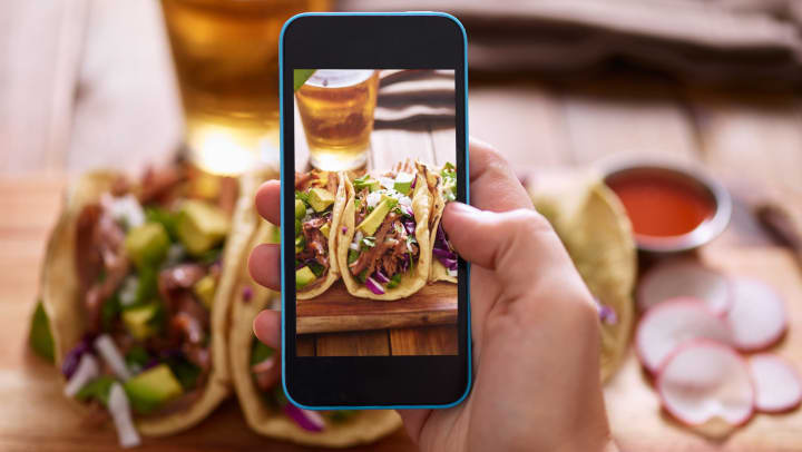 View of a hand holding a smartphone and taking a picture of a plate of tacos and a glass of beer