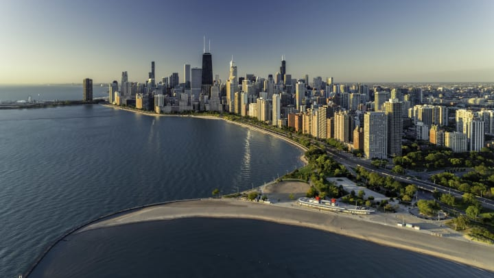 An aerial view of the downtown Chicago skyline, with a park and beach in the foreground.