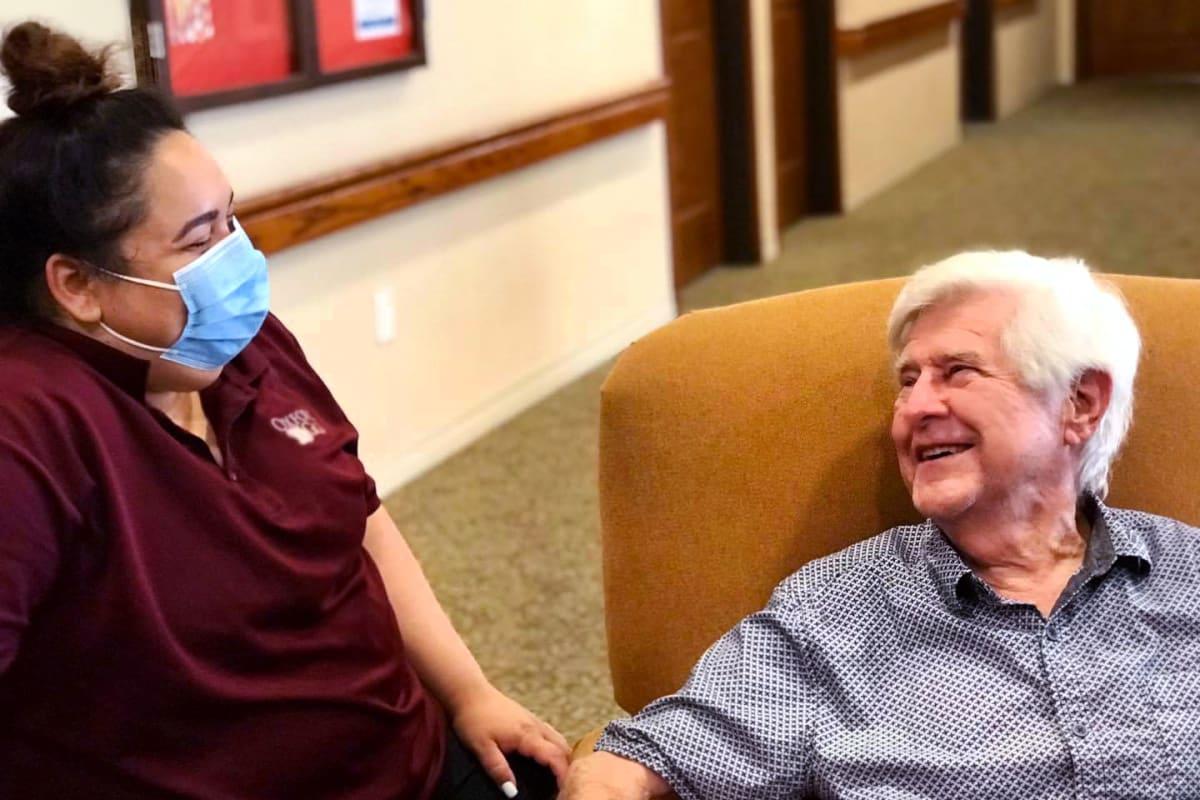A resident talking to a masked caretaker at Oxford Senior Living in Wichita, Kansas