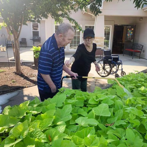 Resident couple outside watering plants at Oxford Glen Memory Care at Sachse in Sachse, Texas