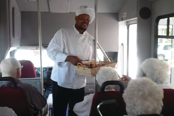 A chef handing out food to residents on the bus at Palms at Bonaventure Assisted Living in Ventura, California