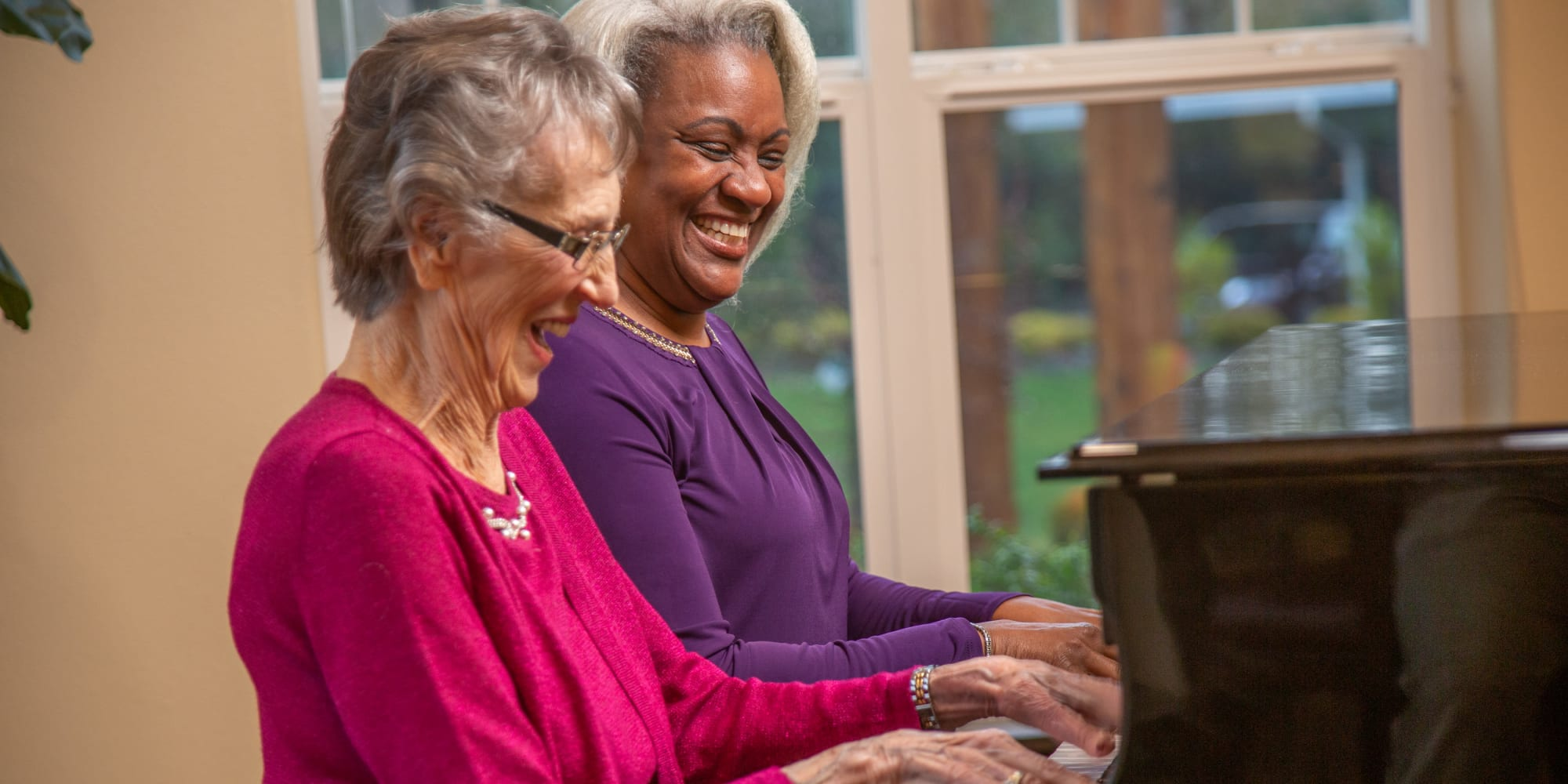 Two residents playing the piano together at Kennedy Meadows Gracious Retirement Living in North Billerica, Massachusetts