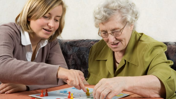 Senior playing board game with caregiver