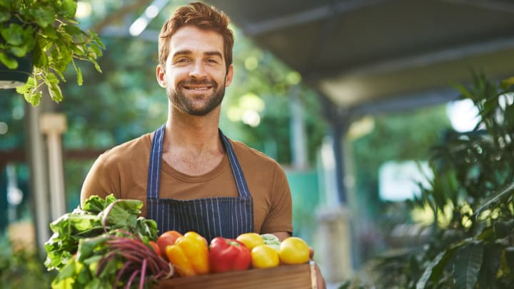 Man wearing an apron and holding a box of fresh vegetables, smiling toward the camera.