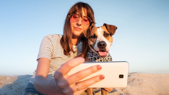 Woman taking a selfie with her dog outside near Cadia Crossing