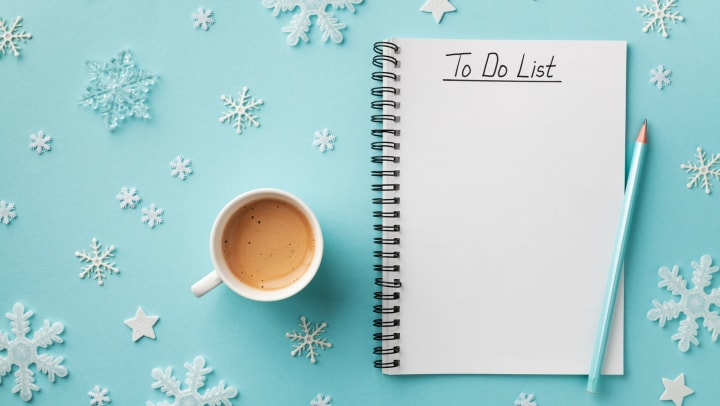 Cup of coffee with To Do List over snowflake/winter-themed background