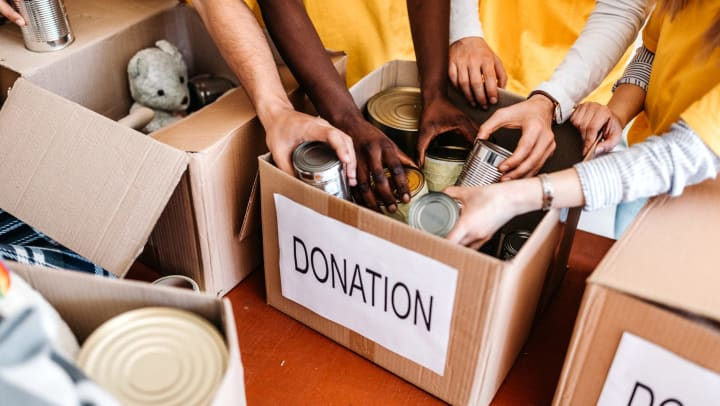 Group of people putting food and item donations into donation boxes