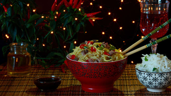 A bowl of noodles in front of a Christmas tree.
