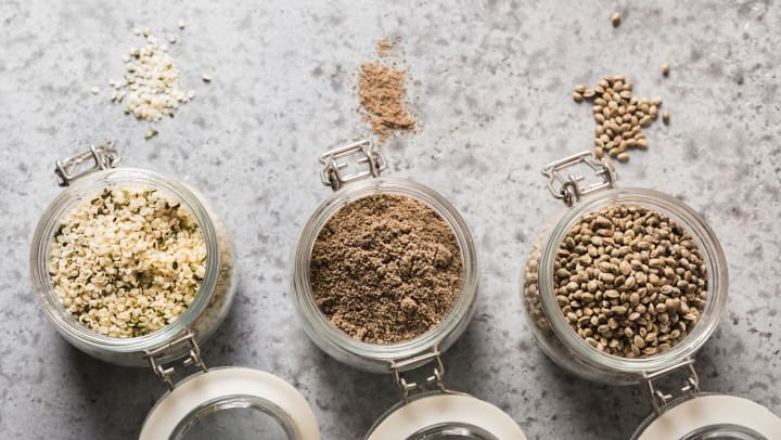 Jars full of hemp seeds, flour and kernels on a gray counter with a small pile of each.