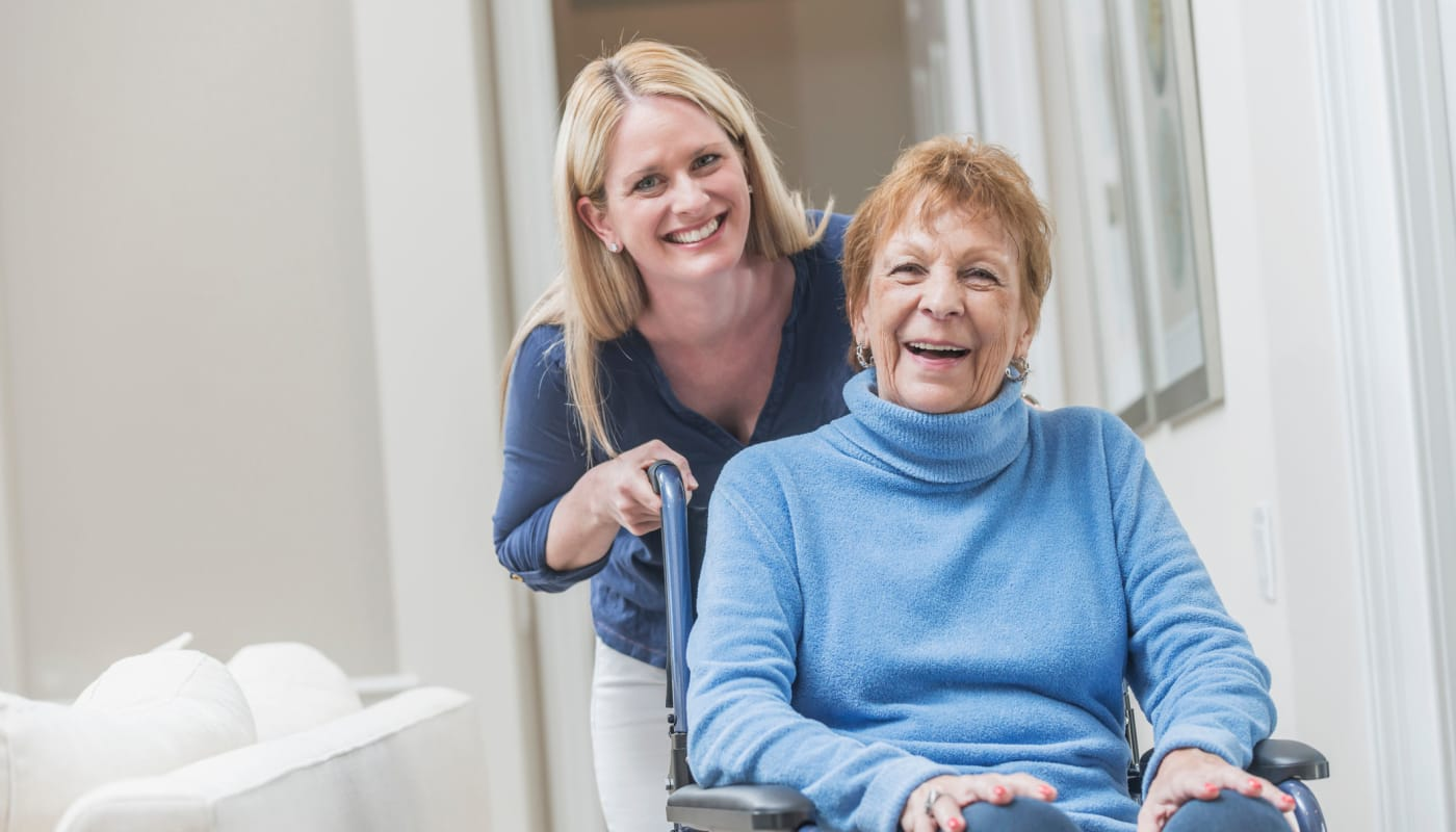 staff member helping a resident in a wheelchair The Preserve of Roseville in Roseville, Minnesota.