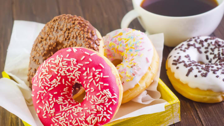 Donuts on parchment paper in a yellow tray with one set on a wooden table next to a white mug full of brown liquid.