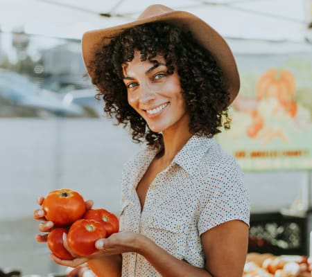 A resident out shopping for tomatoes at a farmers market near Esplanade Apartment Homes in Riverside, California