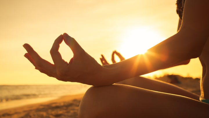 Woman sitting on the beach meditating during sunset near Odyssey Lake Apartments