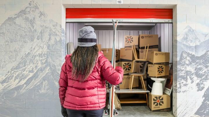 Two men organizing outdoor gear inside a self storage unit