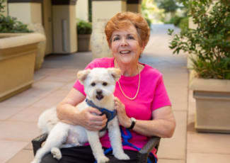 A resident with her dog at Sunset Lake Village Senior Living in Venice, Florida