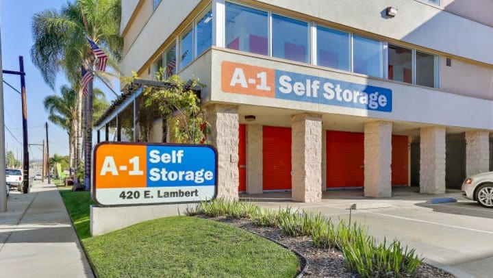 The entrance to A-1 Self Storage in La Habra, CA, features drive-up self storage units, parking spaces, and some tastefully minimalist shrubbery.