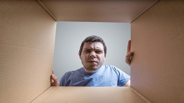 man looking into box to figure out how to prevent mold in storage containers