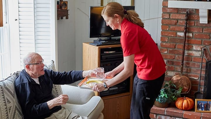 Rhythms Home Care team member serving a meal