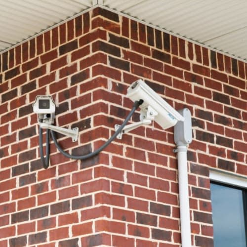 Security cameras mounted on a brick wall at Red Dot Storage in Woodstock, Illinois