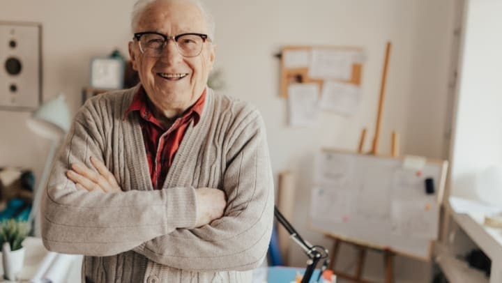 Elderly man crossing arms and smiling at camera