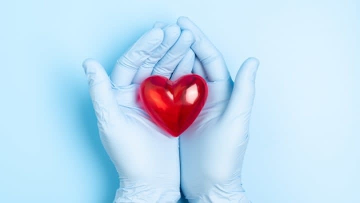 Blue Gloves holding a red fake heart