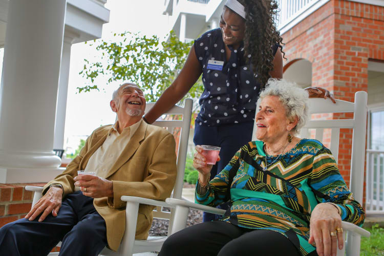 A caregiver speaking with two residents outside at Harmony Senior Services in Charleston, South Carolina