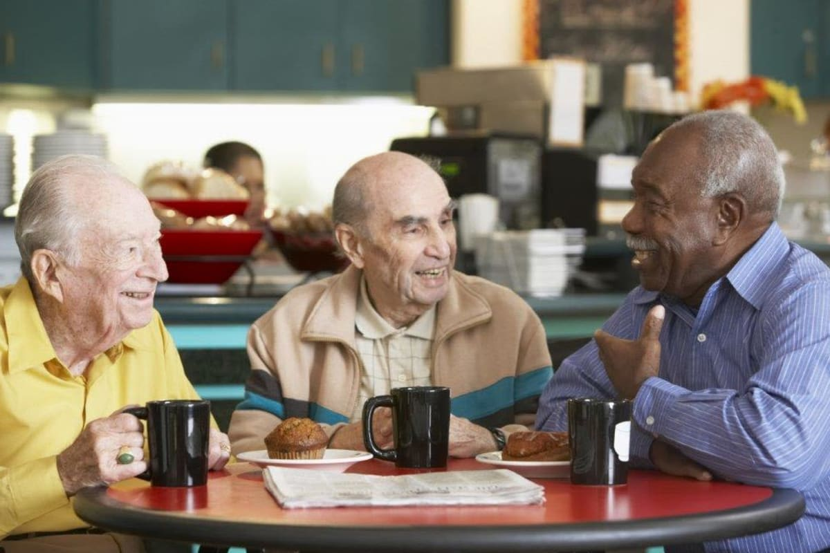 Three residents catching up over coffee at Avenir Memory Care Westside in Los Angeles, California.