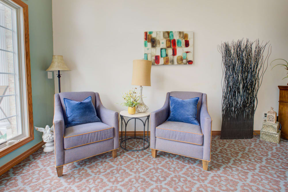 Double armchair seating with lamps and art at Brookstone Estates of Vandalia in Vandalia, Illinois