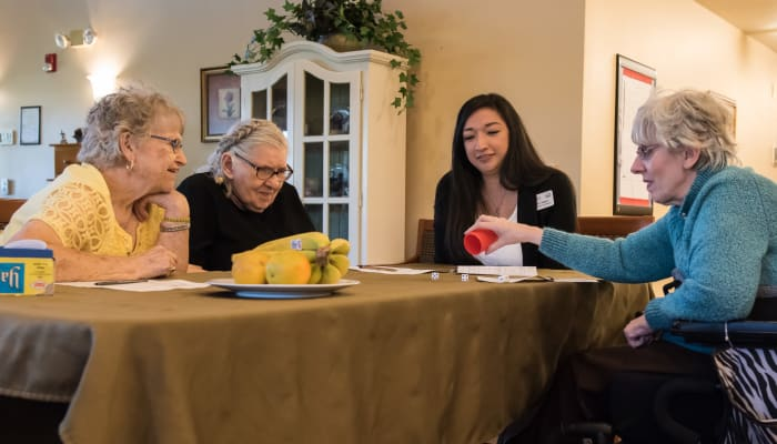 Group of residents and caregiver on a game night at The Springs at Willowcreek in Salem, Oregon