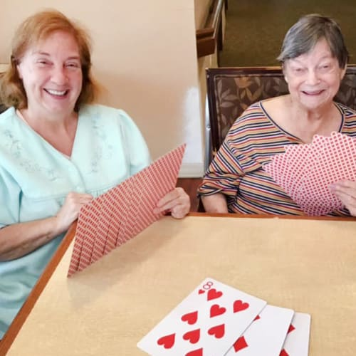 Resident friends playing cards Oxford Glen Memory Care at Grand Prairie in Grand Prairie, Texas