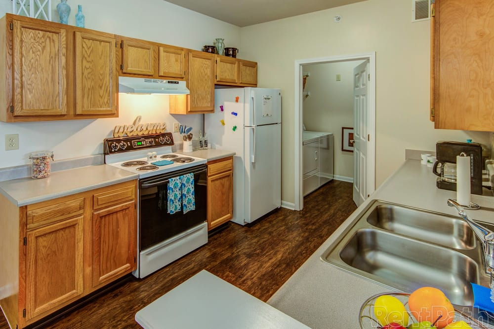 Large kitchen area with light wood style cabinets at Aspen Pines Apartment Homes in Wilder, Kentucky