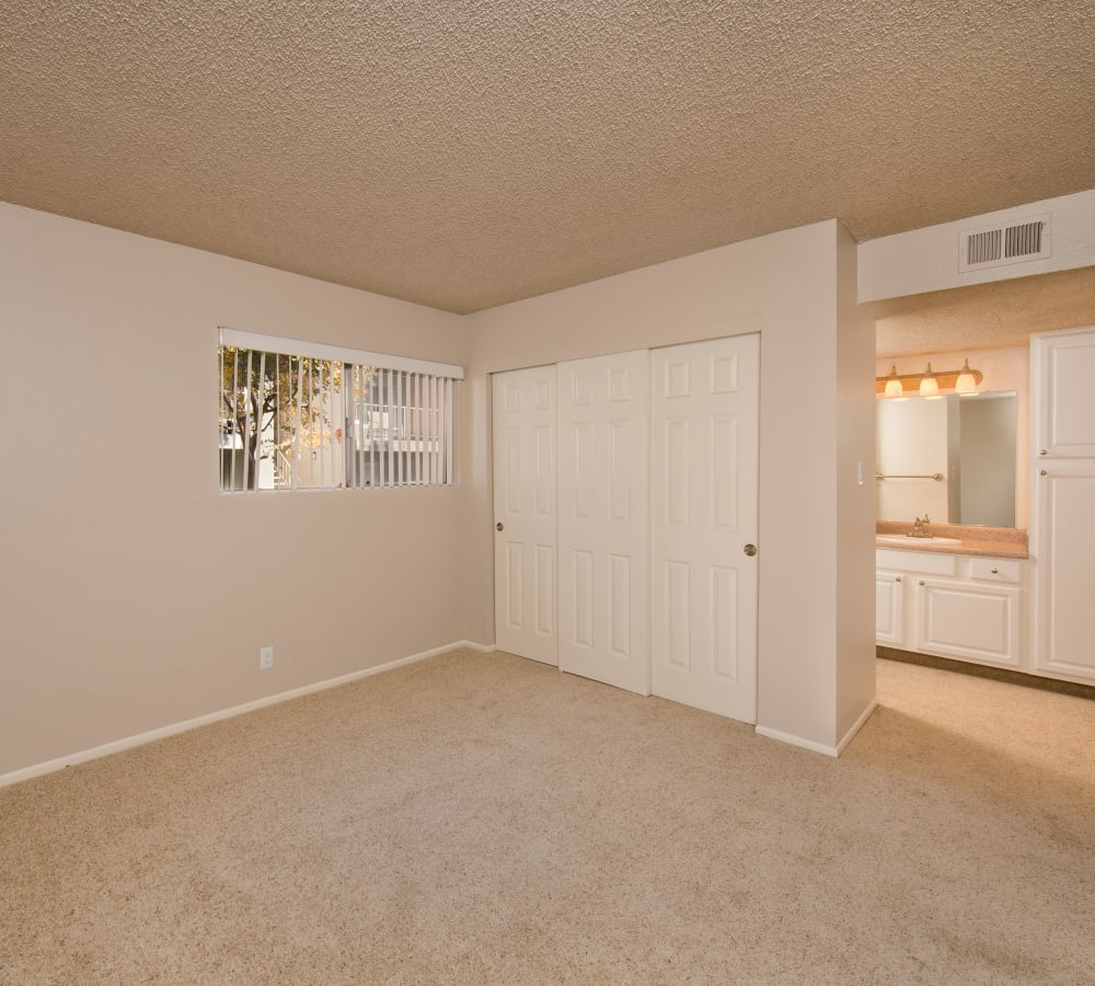 Large master bedroom with blush carpeting at La Valencia Apartment Homes in Campbell, California