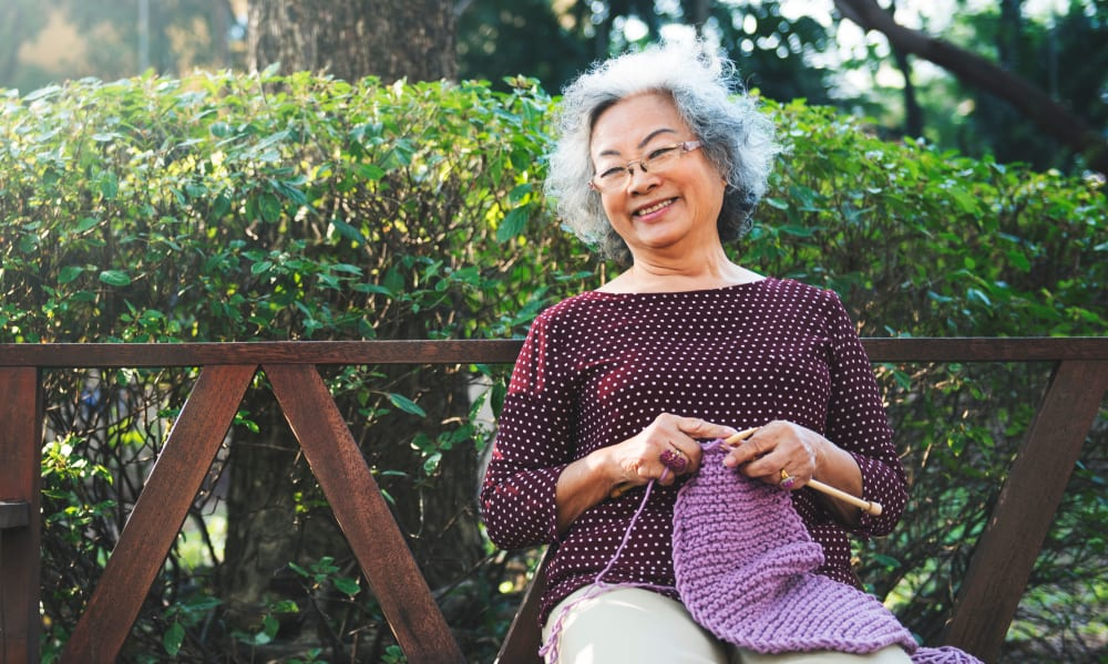Senior woman knitting on a bench at Randall Residence of Sterling Heights in Sterling Heights, Michigan