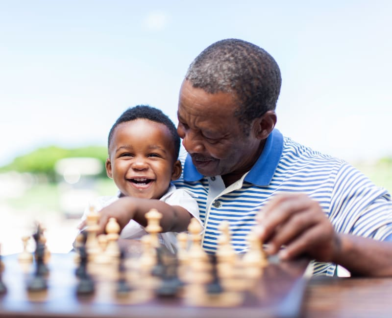 Grandfather and grandson playing chess at The Sanctuary at Brooklyn Center in Brooklyn Center, Minnesota