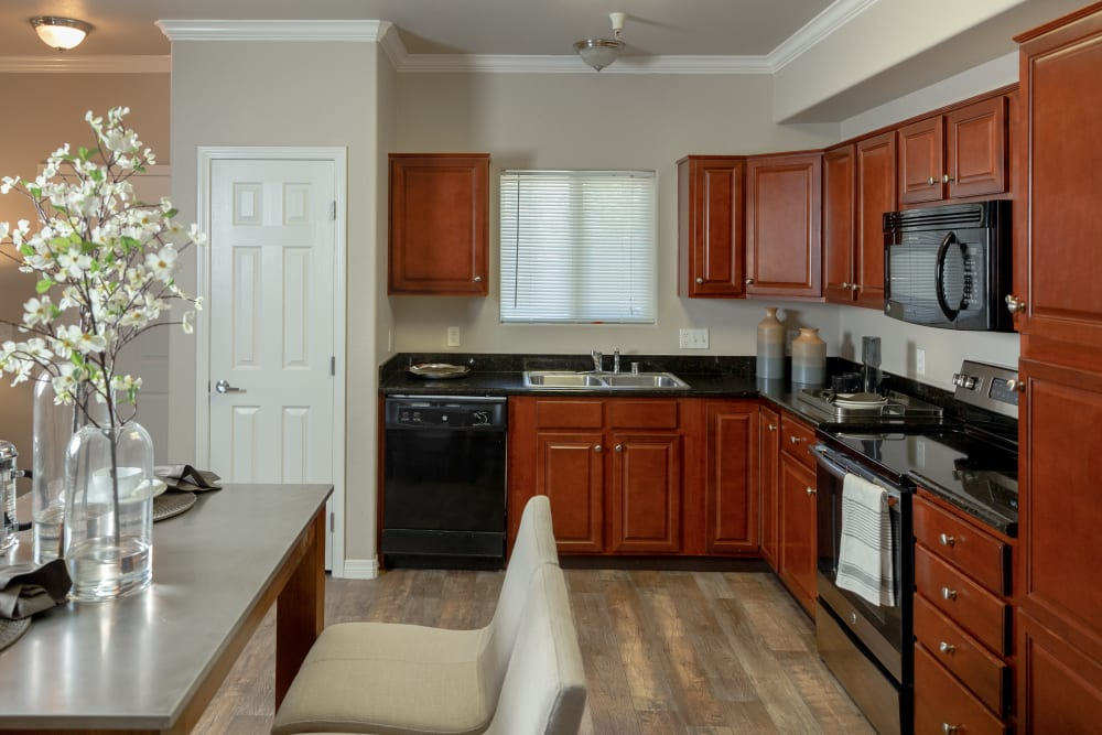 Apartment kitchen with black appliances at Wolf Ranch Condominium Rentals in Sacramento, California