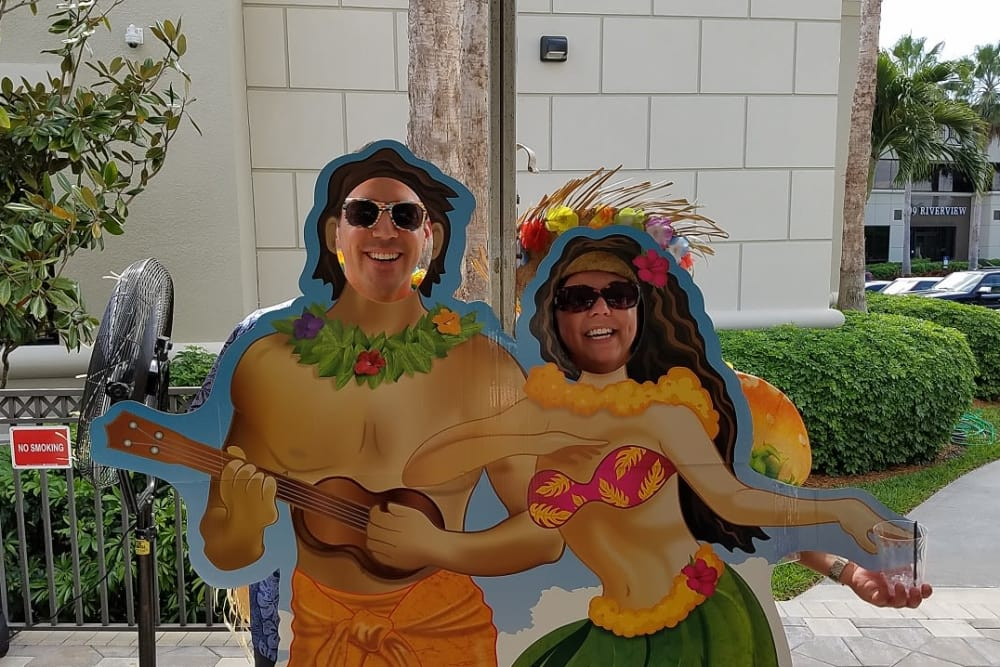 Two people standing in front of Hawaiian cutouts for a photo near Discovery Senior Living in Bonita Springs, Florida