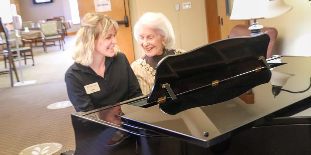 Resident playing the piano with a caregiver at The Springs at Mill Creek in The Dalles, Oregon