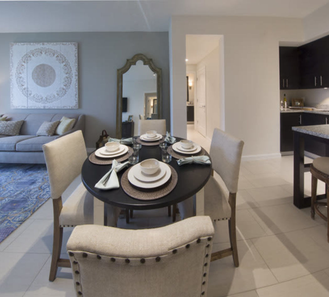 Spacious open floor plan with tiled floors in a model home at Town Fontainebleau Lakes Apartment Residences in Miami, Florida