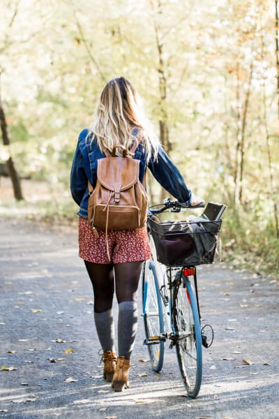 Resident walking her bike down a beautiful tree-lined street near The Alcott in Denver, Colorado