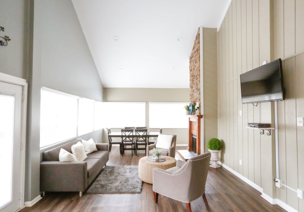 Clubhouse lounge area with a tv and couches for residents to hang in at The Flats at Arrowood in Charlotte, North Carolina