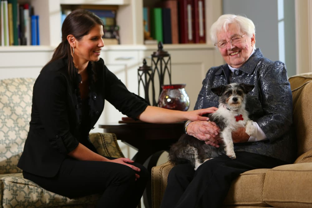 Cheerful resident with her dog and a friendly staff member at Brookstone Estates of Robinson in Robinson, Illinois